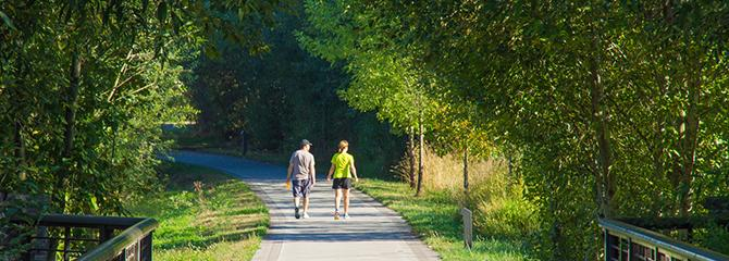 Photo of a couple walking on the Burnt Bridge Creek Trail