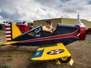 A boy plays in a small replica toy airplane