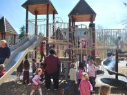 Photo of children and parents playing on the playground equipment in the park
