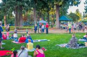 Families and neighbors sit together on the grass enjoying Movie Night in Evergreen Park