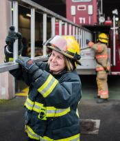 A female firefighter at a training exercise with her crew