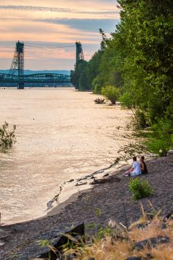 Photo of a couple sitting on the bank of the Columbia River
