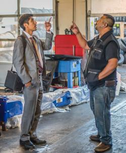 A man in a suit meets with a small-business owner in a Fourth Plain auto shop, offering technical assistance