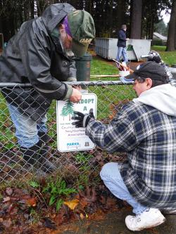 Adopt-A-Park volunteers installing a recognition sign at Countryside Woods Park