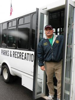 Volunteer Roger on the front step of a Parks & rec shuttle