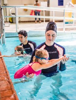 Water safety instructors assist young swimmers in the Marshall Pool