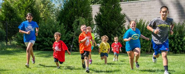 Campers running in the back lawn of Firstenburg Community Center