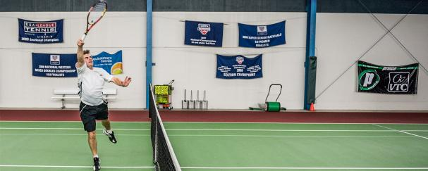 Man hitting a volley during a tennis match at Vancouver Tennis Center