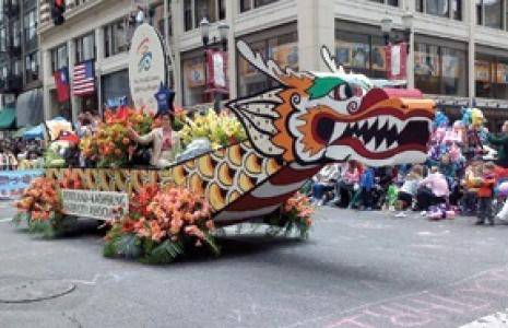 Dragon parade float with colorful flowers.