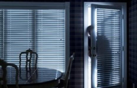 An unwanted visitor entering a dark house.