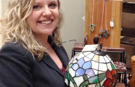 Blonde woman in a black blazer holding a stained glass lamp.