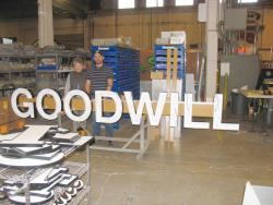 Lynn Miller and Adam Wallis, production manager at Vancouver Sign Group, display recent LED install for Goodwill at company's facility in Vancouver.